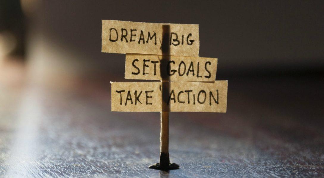 Financial resolutions handwritten on mini flags: dream big, set goals, take action.