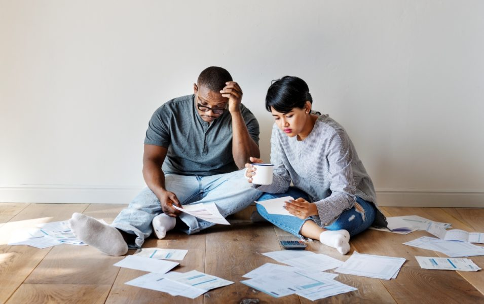 Creating a budget together, a young couple sits on the floor surrounded by papers and a calculator.