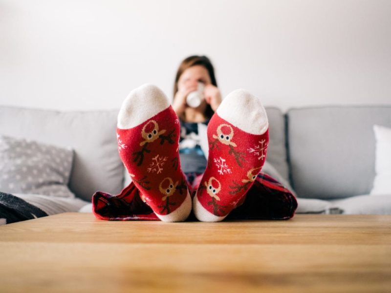 After saving money for Christmas, a woman relaxes with her feet up in reindeer socks, sipping hot chocolate.