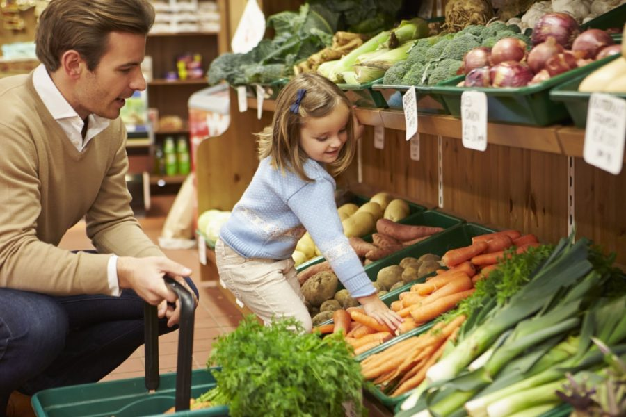 A dad teaching his daughter about money while grocery shopping for vegetables.