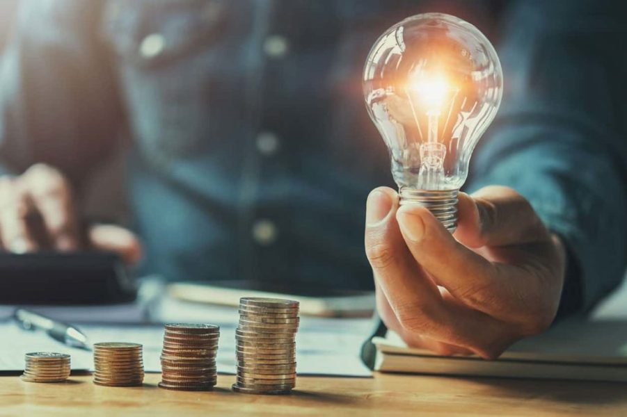 Four stacks of coins and a glowing lightbulb representing ideas for ways to save money.