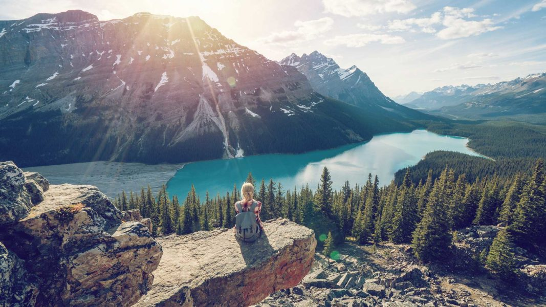 Young woman reflecting at the top of a mountain after credit counselling led her to financial stability.
