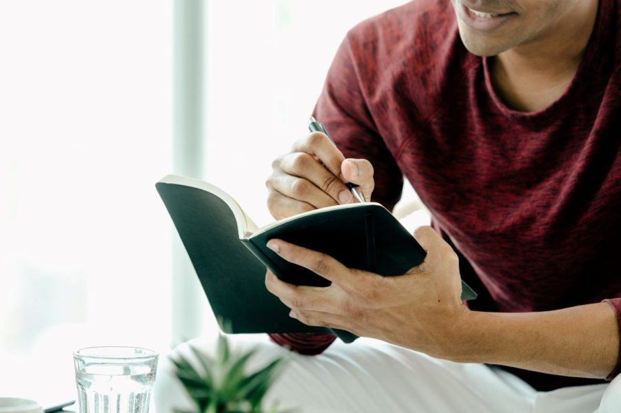 Man writing an entry into his spending journal